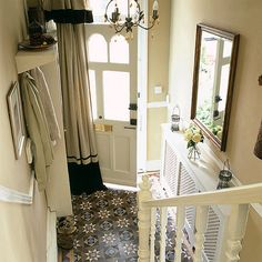 LOVELY entrance: Floor to ceiling drapes against a patterned floor.