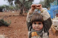 Harrowing: Taken at the Atmen refugee camp on Syria's border with Turkey, the image shows the young Adi Hudea frozen in fear with his arms raised and his lips tightly pursed