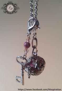 Käfig mit einer rosaen Klangkugel gibt ihrem Träger Hoffnung und hat eine beruhigende Wirkung in schweren Zeiten.