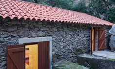 Down on the banks of a beautiful creek sits a beautiful and modern refuge that blends in with its environment. Ansião-based architecture practice Bruno Lucas Dias designed this rentable lodge constructed with recycled materials from an old watermill. Nestled in Portugal's Ponte de São Simão, the contemporary home, called Watermill on the Crag (Moinho das Fragas), was constructed on a modest budget and saves costs with its energy-efficient design.