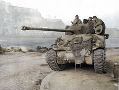 Lieutenant Robert Boscawen on the left with radiophones, commander of 2 Troop, 1st Battalion, Coldstream Guards, Guards Armoured Division, XXX Corps, in a Sherman Firefly IC Hybrid with a 17-pounder anti-tank gun as it's main armament, Patrolling the river Muese at Namur in Belgium. Monday, December 25, 1944
