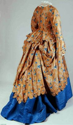 Afternoon gown, French (?), ca. 1870-75. Light brown silk printed with blue leaf and coral motif. High-necked bodice with long, wide sleeves; half-length skirt with back side drapery. Mode Museum, Antwerp