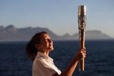 RMS St. Helena Purser Accountant Lyn Buckley holds the Queen's Baton on board the RMS St. Helena in front of Table Mountain at the beginning...