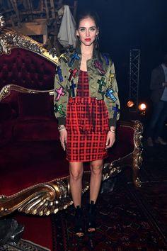 Chiara Ferragni wears a cross-print bomber jacket, plaid dress, and boots