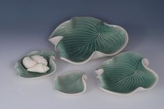 Hosta Leaf Porcelain Pottery Bowl in Green by whiteearthstudio on Etsy.   This useful hand built Hosta leaf bowl can serve many purposes. It is a wonderful centerpiece, fruit bowl, candleholder or vessel to float flowers. I love to float peonies or roses in mine. It also makes a beautiful wedding gift or gift for any occasion. I often sell it as a gift for a gardener. The Hosta bowl is glazed with a glossy celedon green glaze on the interior and a satin matte white glaze on the exterior. It…