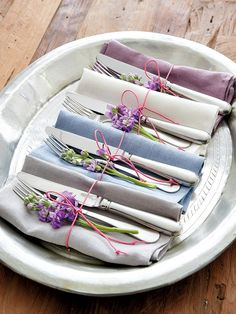 Silverware and cloth napkins wrapped in pretty twine with a sprig of lilac flowers... ᘡղbᘠ