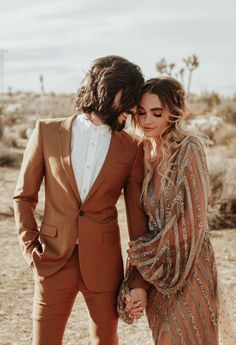 This terra cotta colored groom's suit + the bride's rose gold and silver dress are perfect desert wedding attire | Image by Karra Leigh Photo
