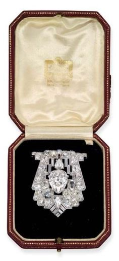 CARTIER - AN ART DECO DIAMOND BROOCH, CIRCA 1925. The shield-shaped brooch set with a pear-shaped diamond weighing 7.74 carats within a pavé-set diamond openwork surround with baguette-cut and pear-shaped diamond detail, 4.5 cm long, signed Cartier, London.