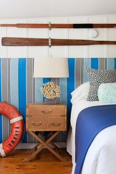 Nautical bedroom features low ceiling over vertical paneled accent wall framing extra-long blue and gray striped headboard accented with black and white fretwork pillows, aqua bolster pillow and blue throw blanket beside wood campaign nightstand topped with oral lamp.