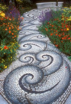 Swirling Sinuous Stone Garden Pathway - Stone walkway in the garden leading to a garden bench, with twists and twirls in pattern, along vibrant flower garden of red, yellow, orange, and purple, inlcuding Geum, Achillea, Salvia perennial plants creates feeling of movement and excitement.