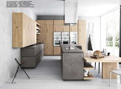 Cloe Kitchen by Cesar: modern metropolitan charm and the timeless beauty of wood blend in this original and unusual arrangement that combines the austere, dark and textured eco cement finish with the vibrant beauty of natural knotted oak. TOGNIN ARREDAMENTI authorized dealer.