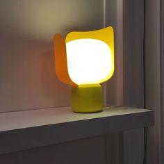 Lampe à poser composée d'une base en aluminium laqué jaune, de pétales en polycarbonate jaune, d'un diffuseur en polyéthylène blanc opalin et d'un câble d'alimentation transparent équipé d'un...