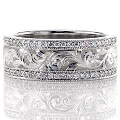 Flora - Flora is an elegant band that uses old world techniques in the form of hand engraving to create a mesmerizing pattern. The design is hand cut in the traditional scroll pattern and raised in relief for a 3D effect. The design is embellished with two rows of micro pavé diamonds that truly capture the light.