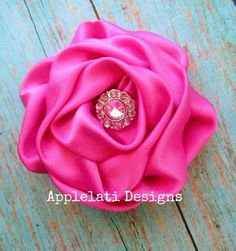 This is a 3.5 inch Hot Pink Satin Rolled Flower and it's topped off with a rhinestone (blingy) button!     ~Perfect for infants, girls, tweens, teens and adults!     ~ This flower is attached to a partially lined alligator clip and can be worn either on a headband or clipped right in your hair!  ...