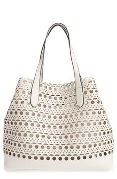 Laser-cut perforations and goldtone hardware make this faux-leather tote both stylish and versatile.