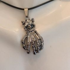 Skull Hand Pendant Stainless steel. Comes on a 16 inch cord. Comes with one free hypodermic needle pen.Price is my lowest Jewelry