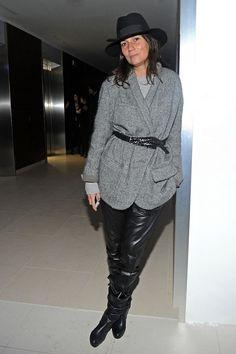 Emmanuelle Alt wears a grey belted jacket, leather pants, and black boots