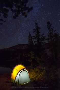 USA: California: Sierra Nevada: Mariposa County: Yosemite National Park: Lower Grant Lake (9250 feet): The night sky filled with stars over a glowing tent perched over a slab of granite overlooking the frigid subalpine lake waters along the southwestern edge © Sean Arbabi | seanarbabi.com (all rights reserved worldwide) #yosemite #lowergrantlake #yosemitenationalpark #sierranevada #backpacking #camping #underthestars  For licensing, fine art prints, and more, visit: http://seanarbabi.com