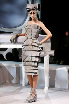 An origami cocktail dress and pill box hat created by John Galliano for Christian Dior.