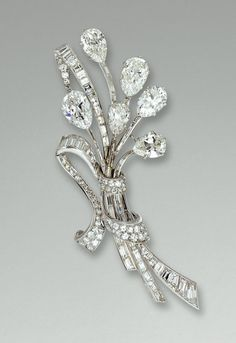 DIAMOND BROOCH, VAN CLEEF & ARPELS, 1950s.     Designed as a stylised ribbon tied spray, set with six principal pear-shaped diamonds, baguette, circular- and single-cut stones, mounted in platinum and white gold,  signed Van Cleef & Arpels and numbered, French assay and indistinct maker's marks, inscribed 'country of origin: France'.