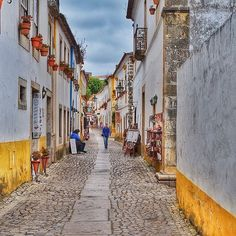 Stamp #628 - Portugal : Get lost in the streets of #Óbidos!  Surrounded by a classic crenellated wall Óbidos gorgeous historic centre is a labyrinth of cobblestoned streets and flower-bedecked whitewashed houses livened up with dashes of vivid yellow and blue paint. Its a delightful place to pass an afternoon but there are plenty of reasons to stay overnight as there's excellent accommodation including a hilltop castle  Thank you @mohitagrawalpics for leaving your #ShareYourStamp!!  For more…
