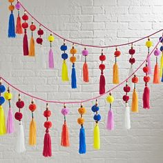 This colorful hanging garland is like a party for your décor. It's adorned with playful tassels, pom poms and wooden beads for a truly festive look.
