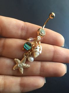Pretty gold plated belly ring with a real seashell, faux pearl, abalone, opal glass, and cz gem starfish dangles. The bar is 14 gauge, 11mm