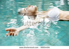 Attractive young woman floating in a swimming pool with her arms outstretched, looking at the sky.