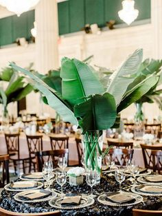 tropical wedding centerpieces photo by Ashley Slater Photography / http://www.himisspuff.com/green-tropical-leaves-wedding-ideas/