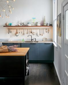 """The Amy says.Orbit Light is from Townsend Design and ships flat. The shelf over the sink is stained walnut with a strip of LED lights underneath. The floor is oak with a dark stain; """"we mixed black with a little brown to get the right shade,"""