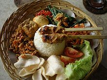 Personal serving of nasi Bali, weaved bamboo plate with rice surrounded by pieces of meat and vegetables side dishes.