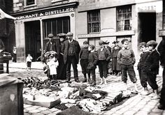 Kids and fathers looking at goods for sale at the Greenmarket stalls in Dundee.  (from http://www.leisureandculturedundee.com/library/circa )