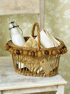 Panier en osier décoré de noix, noisettes et marrons attachés comme une guirlande tout autour