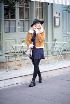 A winter get-up with a brown jacket, black tights, blue flow dress, and black ankle boots | Media Marmalade