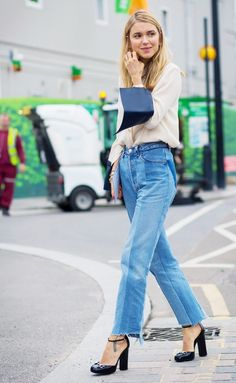 A chiffon button-down blouse is worn with high waisted raw hem jeans, black ankle strap heels, and gold minimal jewelry.