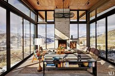 Studhorse by Olson Kundig in Winthrop, WashingtonThe ranch, nestled in the Cascade mountain range, comprises three steel, barn wood, and glass pavilions centered on a giant boulder. The main pavilion (shown) contains living, dining, and kitchen areas, each enclosed with window walls to optimize views of the surrounding landscape.