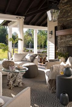 Outdoor drapery helps blur the lines between indoor spaces and exterior porches filled with upholstery, swings and places for lazy napping next to the saltwater pool, all keeping a fresh, clean and neutral palette. And after the sun goes down, the party moves to the lakeside fire pit. Everything is upholstered in Sunbrella, including the outdoor drapery, which all gets a heavy hose-down in advance of every visit. The couple and their guests can nap, lounge, party and relax there. We're…