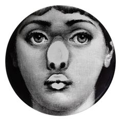 'Themes and Variations wall plate No. 254'  Piero Fornasetti's graphic art often re-worked a single idea over and over again, allowing his imagination to run free to develop new concepts. The most famous of these ideas - the Themes and Variations, illustrated variations on the image of an enigmatic, almost Mona Lisa-like face of a woman. The woman was Lina Cavalieri, whose face Fornasetti found while glancing through a 19th Century French magazine.