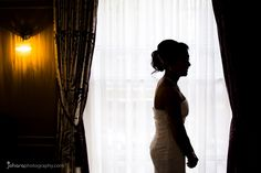 Silhouette of bride wearing a white dress in the window.
