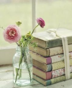 A stack of pretty vintage books and flowers in Jam jars can make a simple but beautiful table centre piece