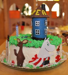 Moomin house cake with moomins dancing around it.