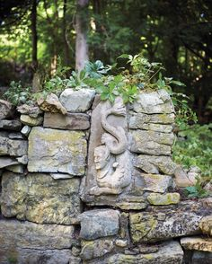 A sphinx-like relief is one of the several decorative features in the evergreen garden.