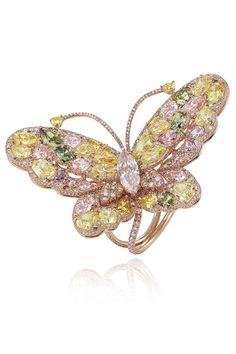 Anillo mariposa en oro rosa engastado con diamantes fancy de colores y un diamante talla marquesa en el centro, de Chopard.