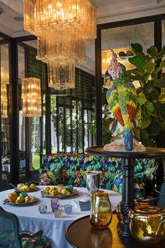 L'ancien consulat de France a Anvers Dans la salle à manger, comme un jardin d'hiver revisité, les vues du jardin se reflètent dans un mur de miroirs et se confondent avec les motifs fleuris de la banquette et les plantes d'intérieur. Le perroquet est en porcelaine de Paris, les lustres en verre de Murano (Mazzega).