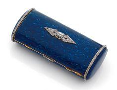NÉCESSAIRE DU SOIR en or jaune 18K (750°/°°) émaillé bleu lapis, de section ovale, appliqué d'un motif géométrique serti de diamants baguettes et de roses, les bords ourlés de roses, l'intérieur recèle