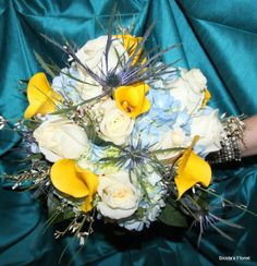 Here is an example of a bridal bouquet with yellow calla lilies, white roses and blue hydrangeas. This bouquet is perfect for a spring or summer wedding!