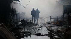 A couple walking in between burned shops in the streets of Grozny