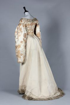 A Charles Frederick Worth brocaded satin Russian court dress, circa 1890, un-labelled, the satin woven with gold silk roses, the front plastron and skirt panels entirely covered with floss silk and pearl beaded roses, the bodice with hanging sleeves edged in silver braid, bust approx 86cm, 34in, waist 66cm, 26in; together with three non-related Russian embroidered panels (qty) Provenance: Sophie Benckendorff (nee Shuvalov) c.1860-1925.