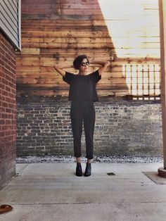 All black outfit of loose trousers with a tee, boots and sunglasses