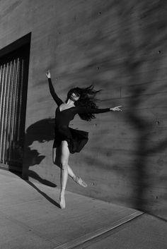 image noir et blanc, femme qui danse, habillé d'une robe noire, avec décolleté en V plongeant, les bras grands ouverts, tels des ailes d'oiseau